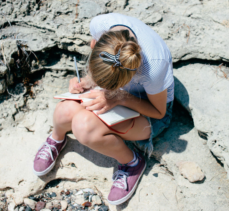Girl writing on notebook sitting on a rock